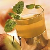 Apfeltee im Glas mit Zitronenmelisseblättchen