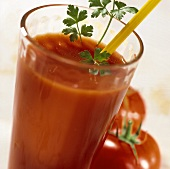 Potato and tomato drink in a glass, two tomatoes beside it