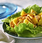 Chicken & pineapple salad on iceberg lettuce leaves; blue plate