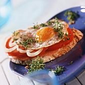 Peasant bread with fried egg, tomatoes, ham and cress