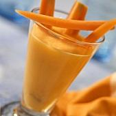 Möhren-Aprikosen-Drink mit Möhrensticks im Glas