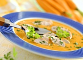 Cream of carrot soup with turkey breast and parsley