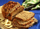 Apple and walnut bread, partly sliced on chopping board