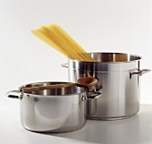 Two pans with wooden spoon and spaghetti