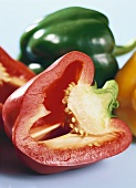 Half a red pepper in front of a green pepper