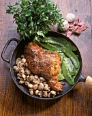 Knuckle of pork with mangetouts & mushrooms in a pan