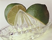 Two lime halves on lemon squeezer