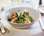 Pea risotto with scampi and watercress in deep plate