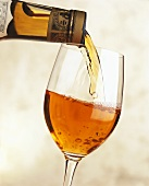 Pouring Pineau des Charentes from a bottle into a glass