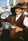 Coachman with tankard & decorated horse at Oktoberfest