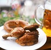 Half a chicken with pretzel on plate, tankard beside it