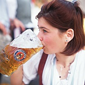 Young woman drinking a litre of beer at Oktoberfest