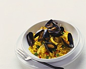 Paella with mussels in deep plate