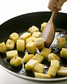 Frying croutons in a pan