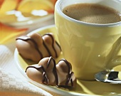 Double nut chocolates on saucer of an espresso cup