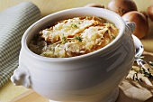 Onion soup with toasted bread & cheese in soup tureen