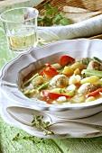 Vegetable stew & dumplings; white wine glass; bread in basket