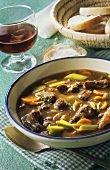 Oxtail soup with white bread and red wine glass