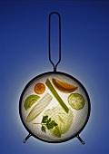 Vegetables, salad leaves & fruit slices under a strainer