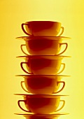 Pile of soup plates against a yellow backdrop