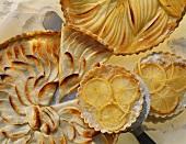 Apple tart (a piece cut), lemon tartlets, pear tart