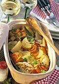 Gemüse-Bäckeoffe in der Auflaufform, dahinter Weissweingläser