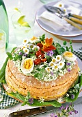 Wild herb cheesecake with edible flowers, eggs, tomatoes