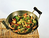 Strips of turkey with vegetables in wok on bamboo tray