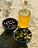Olive oil and two bowls of black and green olives