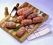 Raw veal roulades with onions and spices on wooden board