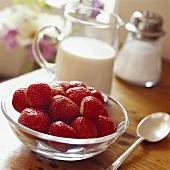 Strawberries in a bowl, jug of cream behind
