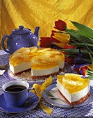 Cheesecake with pineapple and a cup of coffee; tulips