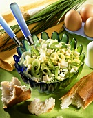 Leek salad with chopped eggs in dish; baguette