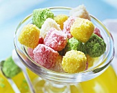 Coloured coconut sweets in glass bowl