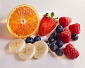 Half an orange, banana slices and various berries