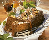 Walnut cake with chocolate icing and chopped pistachios