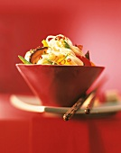 Asian noodles with vegetables in a red bowl