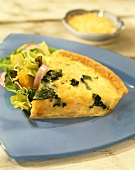 A piece of potato and spinach quiche with lettuce on plate