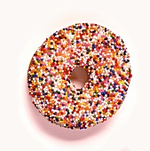 Doughnut with coloured sugar pearls on white background