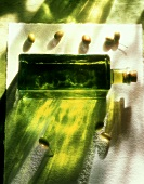 A bottle of olive oil and fresh green olives
