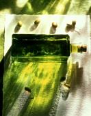 Eine Flasche Olivenöl und frische grüne Oliven
