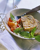 Cheese & ham terrine with tomatoes and basil on plate