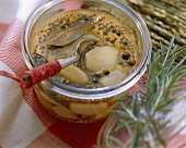 Spicy pickled garlic with bay in a preserving jar