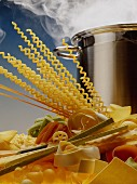 Various pastas in front of a steaming pan
