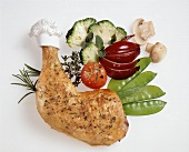 Chicken leg and vegetables on a white background