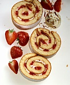 Three slices of strawberry roulade with cream & chocolate curls