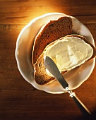 Bread and butter on a plate with a butter knife