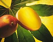 Whole and half mango on a green leaf