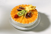 Peach cream gateau with exotic fruit on marble plate
