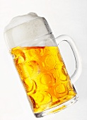Light beer with head in glass tankard